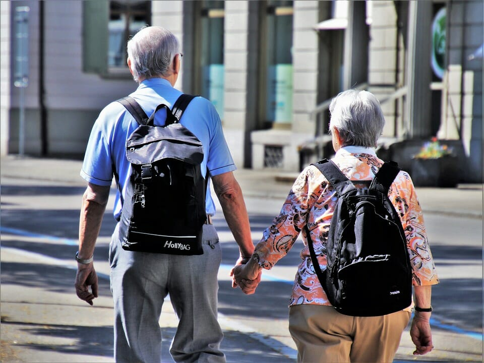 Old couple with backpacks holding hands