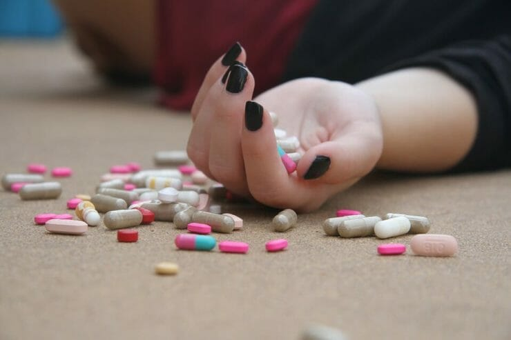 Teen girl's hand limp with pills spread around it