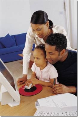 Parents and little girl on the computer