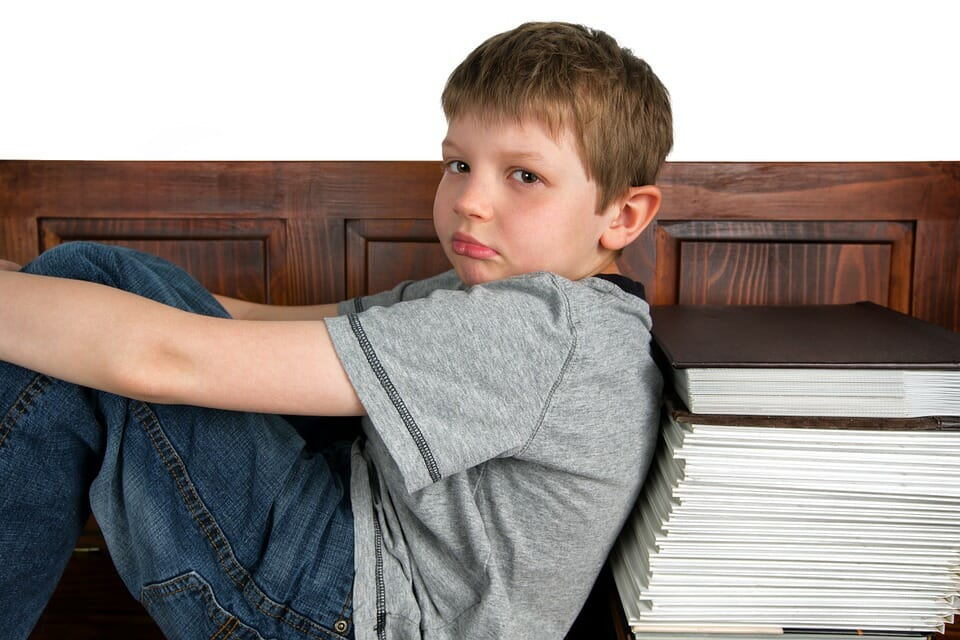 Boy leaning against a stack of books looking sad