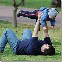 Parent raising child happily in the air