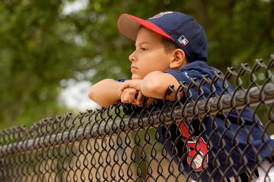 Boy in baseball outfit watching a game