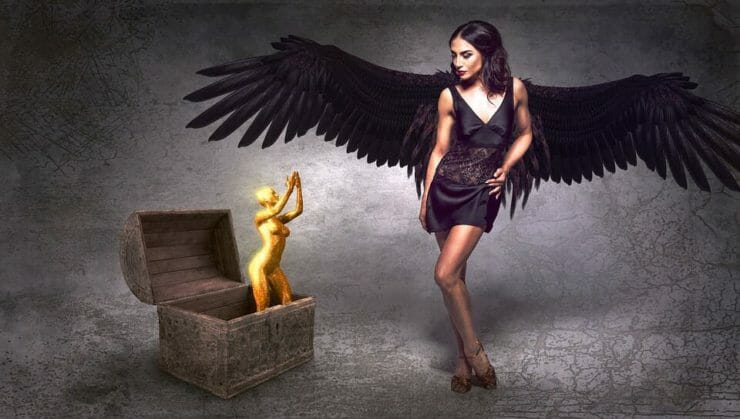 Dark angel looking over box with golden figure inside it