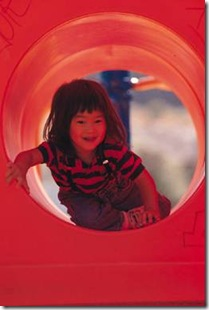 Happy girl in playground tunnel