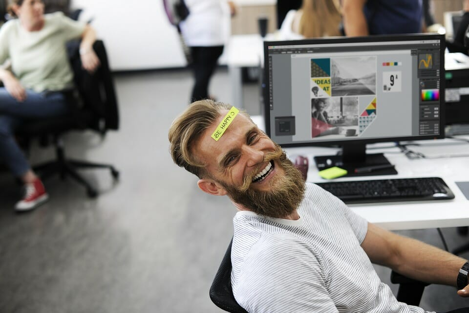 "Man in office smiling with ""Be Happy"" sticker on his forehead"