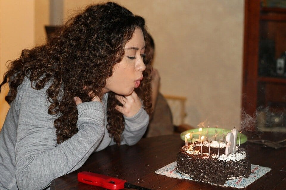 Teen girl blowing out candles on a cake at a birthday party