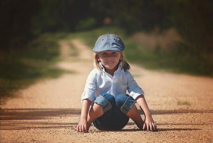 Boy sitting on a dirt road