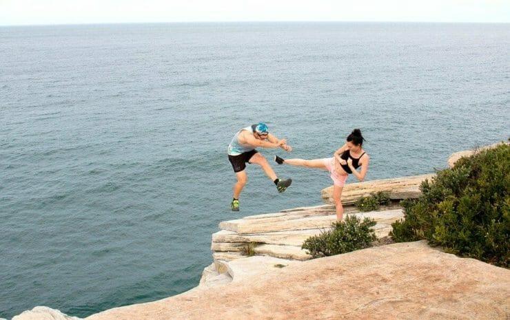 Woman kicking man off a cliff