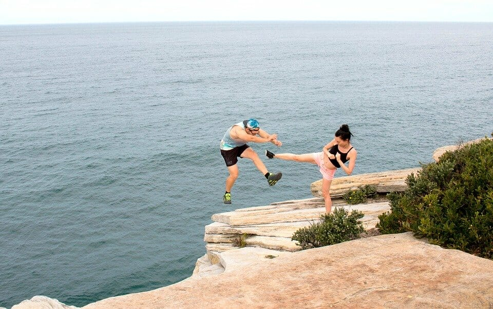 Woman kicking man off a cliff