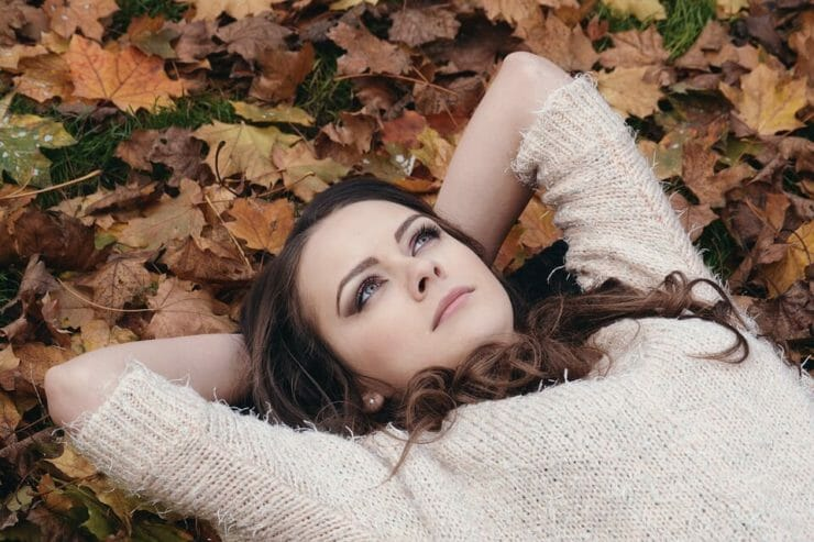 Young woman lying peacefully on a bed of leaves