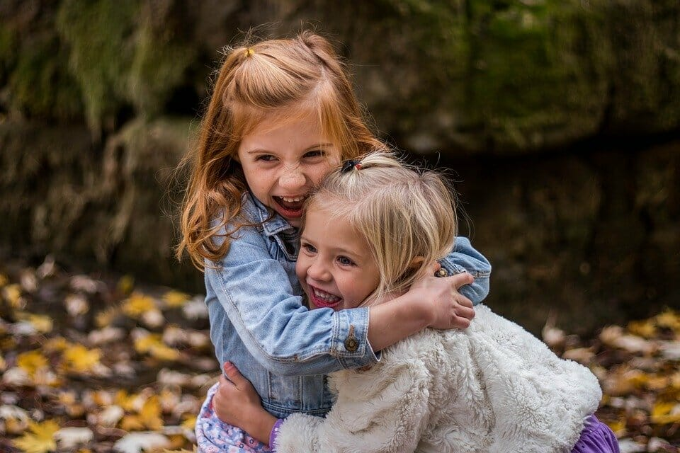 Girl hugging younger girl aggressively