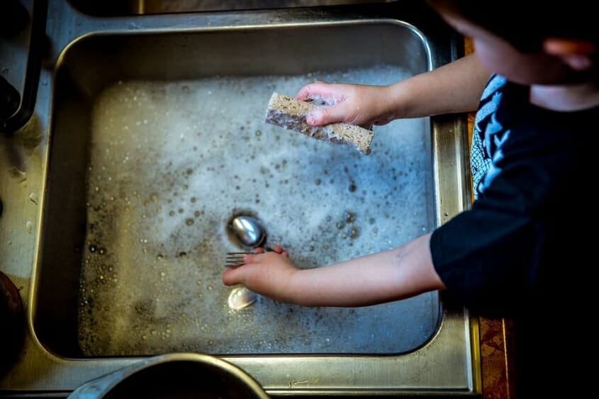 Young child washing dishes