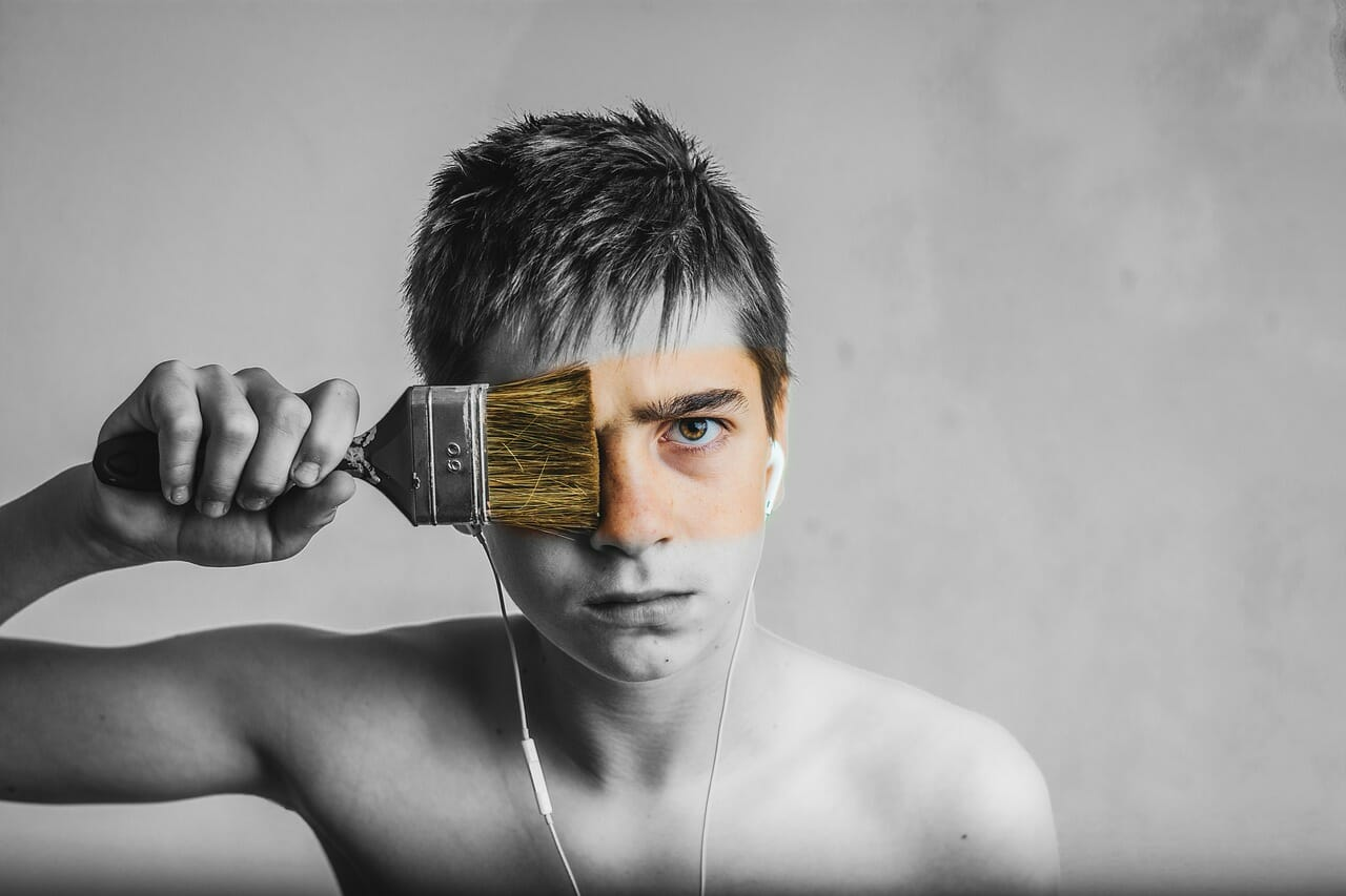 Young man painting face with brush