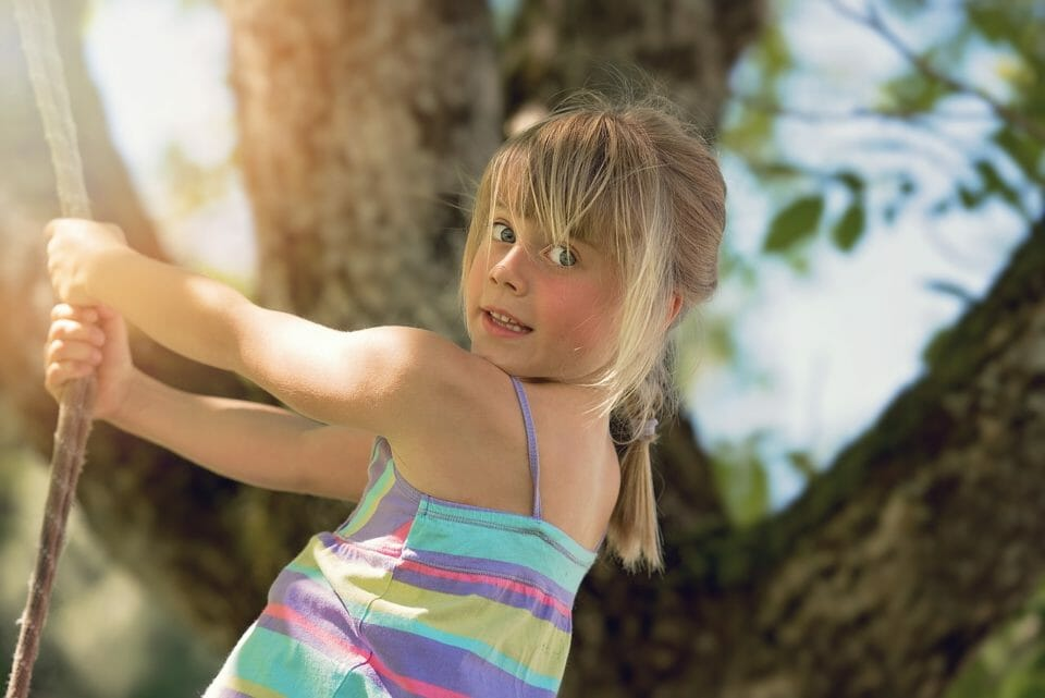 Girl swinging from a rope