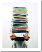 Person holding a high stack of documents