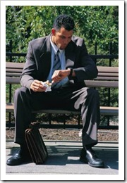 Man sitting on bench eating a sandwich