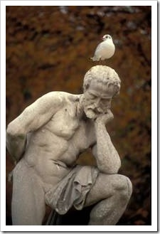 Greek statue of pondering man with bird on his head