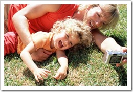 Mother and child laughing on grass