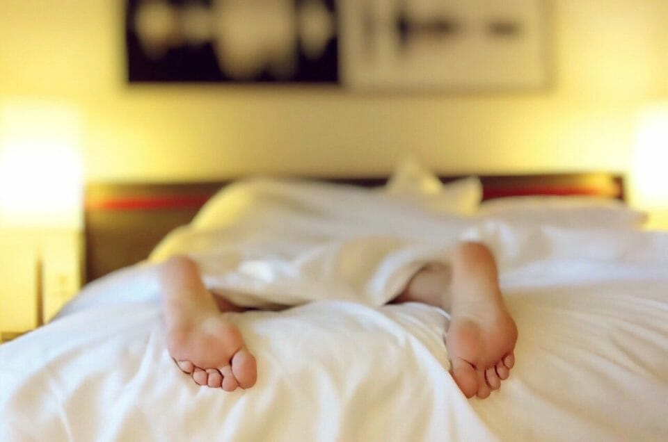 Person's feet sticking out of bed