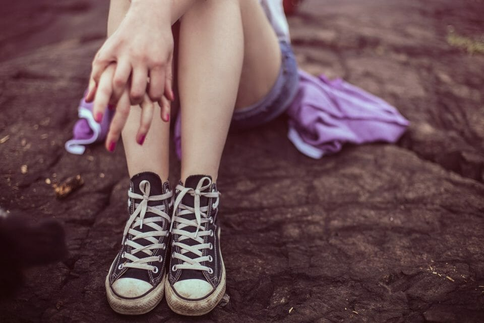 Teen girl's legs in Converse shoes