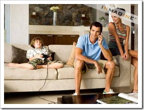 Kid playing video game next to parents