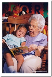 Old woman reading a story to a girl