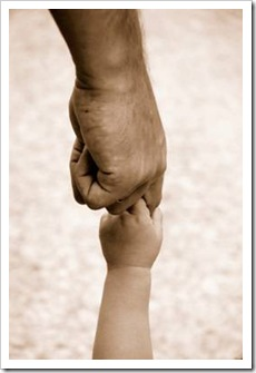 Grown up hand holding baby hand
