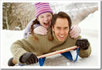 Father sledding with daughter