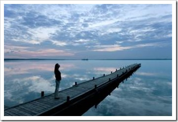 Woman on long pier at dusk