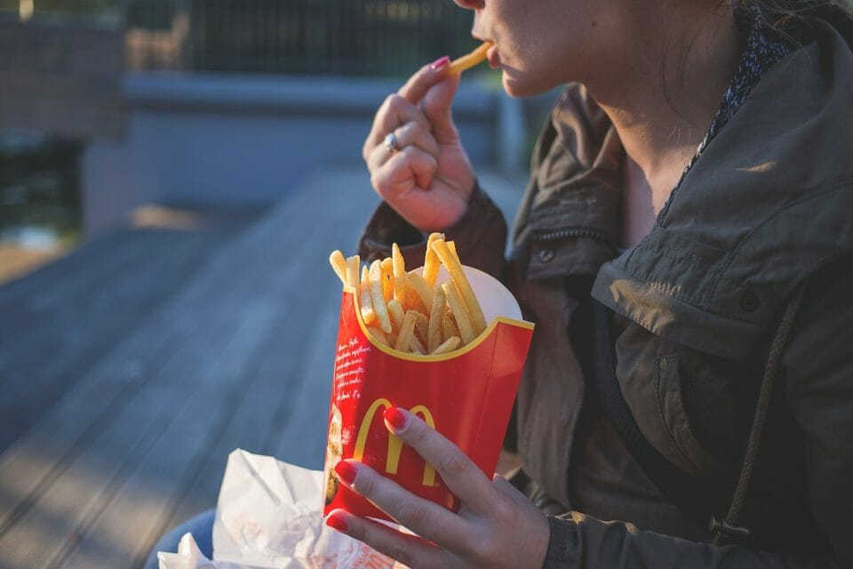 Woman eating McDonald's french fries - the ultimate fast food