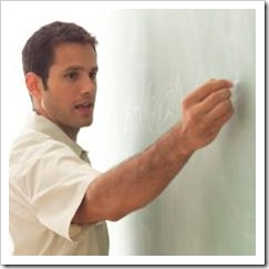 Young male teacher writing on board