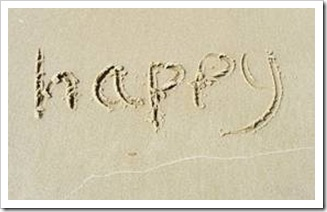 Happy written in sand