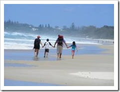 Family walking on a beach holding hands