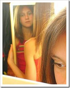 Teen girl looking in mirror