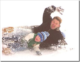 Father and son sliding in snow