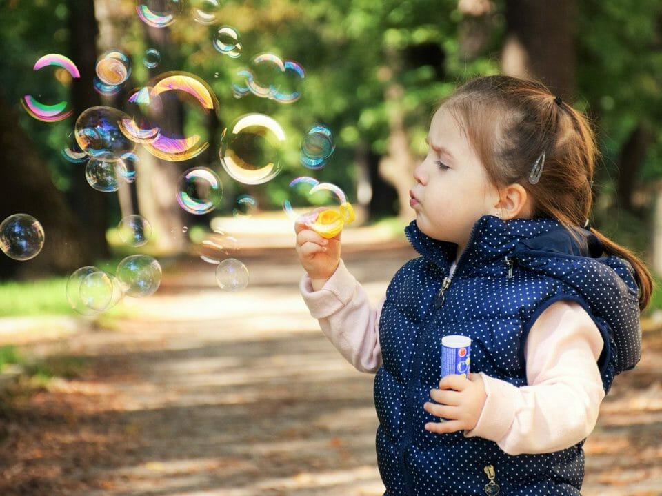 Little girls blowing bubbles and making happy childhood memories