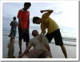Group of boys hitting fat boy on beach