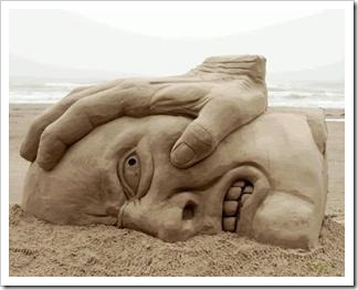 Sand sculpture of head pushed down
