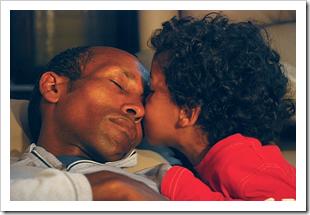 Toddler kissing his sleeping dad
