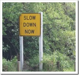 Slow down now sign