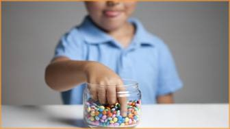 Boy taking candy out of a jar