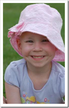 Little girl smiling in big hat