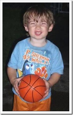 Boy holding a basketball and making a face