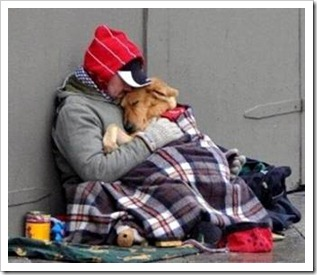 Homeless man hugging his dog