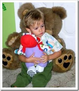 Sad little boy hugging a doll