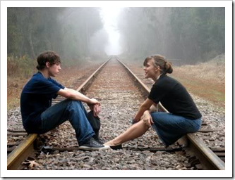 Teenagers talking on railroad tracks