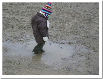 Little kid in a puddle of mud