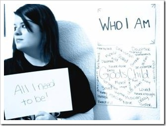 "Girl holding a sign saying ""Who I am - All I need to be"""