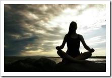 Women meditating on rocks