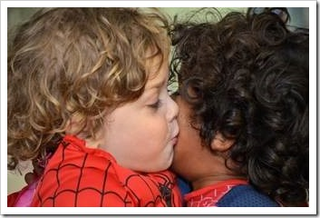 White boy kissing a black boy on the cheek